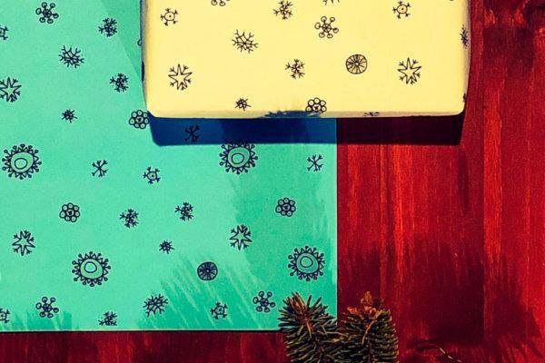 Geschenk mit neogrün Geschenkpapier im Schneeflockendesign auf Tisch